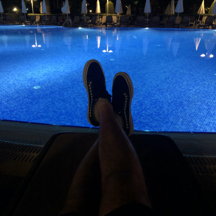 my feet resting on a lounge chair in front of a pool at night